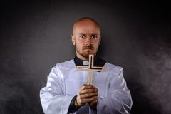 Catholic priest in white surplice and black shirt. With cleric collar holding wooden cross and praying royalty free stock photo