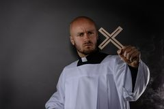 Catholic priest in white surplice and black shirt. With cleric collar holding wooden cross and praying royalty free stock images