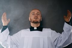 Catholic priest in white surplice and black shirt with cleric collar praying. With hands raised up stock images