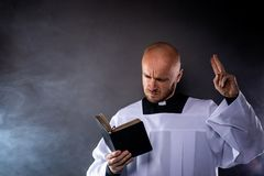 Catholic priest in white surplice and black shirt with cleric collar reading bible. And preaching a sermon stock photos