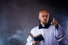 Catholic priest in white surplice and black shirt with cleric collar reading bible. And preaching a sermon royalty free stock image