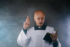 Catholic priest in white surplice and black shirt with cleric collar reading bible. And preaching a sermon stock photo