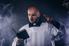Catholic priest in white surplice and black shirt with cleric collar reading bible. And preaching a sermon stock images