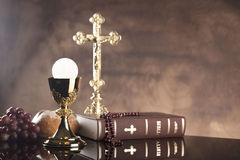Catholic religion theme. Holy Bible, the cross and gold chalice on glass table and stone background stock photos