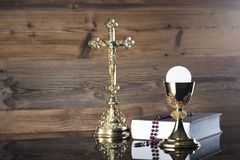 Catholic religion theme - holy communion concept. Holy Bible, the Cross, golden chalice and rosary on wooden background.  Place for text Royalty Free Stock Image