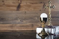 Catholic religion theme - holy communion concept. Holy Bible, the Cross, golden chalice and rosary on wooden background.  Place for text Stock Image