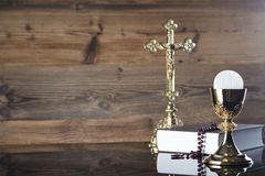 Catholic religion theme - holy communion concept. Holy Bible, the Cross, rosary and golden chalice  on wooden background and glass table.  Place for text Royalty Free Stock Photo