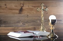 Catholic religion theme - holy communion concept. Holy Bible, the Cross, rosary and golden chalice  on wooden background and glass table.  Place for text Royalty Free Stock Image