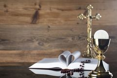 Catholic religion theme - holy communion concept. Holy Bible, the Cross, rosary and golden chalice  on wooden background and glass table.  Place for text Stock Photos