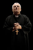 Catholic reverend holding a wooden cross. Isolated on black background Stock Photos