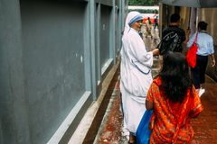 Catholic Sister is talking with children in front of House of Mother Teresa in Kolkata, India.  stock photo