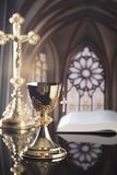 Catholic theme. Catholic holidays – Easter. Catholic concept background. The Cross, Holy Bible. Golden chalice on the altar Royalty Free Stock Photography