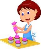 Catoonvrouw die met schort cupcakes verfraait stock illustratie