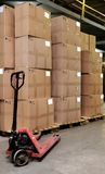 Catron boxes and pallet truck in warehouse. Group of carton boxes and manual fork pallet truck in warehouse stock photo