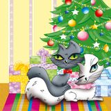 Cats. Couple of cats lying on rainbow-like carpet next to a christmas tree Royalty Free Stock Photography