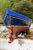 Cats Sheltering Under a Boat. A number of cats sheltering under a colourful wooden Greek fishing boat propped up on shore for painting and maintenance, Thassos Royalty Free Stock Photos