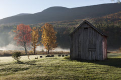 Catskill Mountain Barn with Autumn Trees. Sunrise in the northern Catkill Mountains, with brighly lit autumn trees and old wood barn with Black Dome Mountain in Royalty Free Stock Images