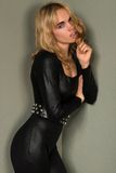 Catsuit. Beautiful young blonde woman in a shiny black catsuit stock photos