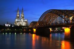 Cattedrale di Colonia con il ponte ferroviario alla notte fotografia stock
