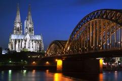 Cattedrale di Colonia con il ponte ferroviario alla notte immagini stock libere da diritti