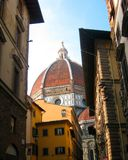 The Cattedrale di Santa Maria del Fiore. View to the famous dome of the Cattedrale di Santa Maria del Fiore behind houses on the nearby street, Florence, Italy Stock Images