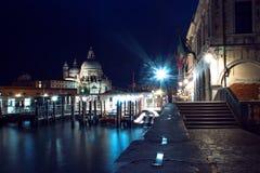 Cattedrale di vista di notte di Santa Maria della Salute e della gondola nella priorità alta a Venezia, Italia Fotografia Stock Libera da Diritti
