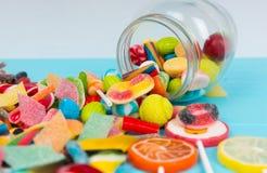 Cattered鲜美糖果和棒棒糖当果子近下落的玻璃 免版税库存照片