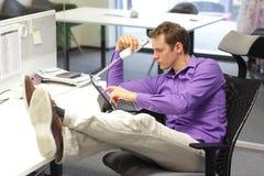Cattiva posizione di seduta - uomo in ufficio Immagini Stock