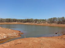 Cattle dam in outback Australia with water in the desert Royalty Free Stock Photo