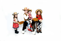 Cattle Drive. Family of four dress up for Halloween as cowboys and cowgirls. The boys are riding a stuffed pony and the girls are leading and bringing up the royalty free stock images