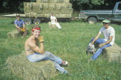 Cattle farmers relaxing on hail bales Stock Image