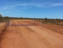 Cattle grid on gravel road in Australian Outback desert Royalty Free Stock Images