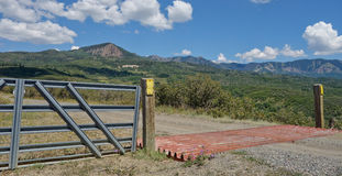 Cattle guard and fence in Colorado mountains. Stock Images