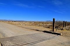 Cattle guard in a desert ranch. Cattle guard, gate, and fence of ranch land in a desert environment Royalty Free Stock Image