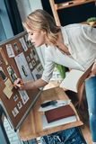 Cattura delle note Scrittura premurosa della giovane donna qualcosa giù sulla t immagine stock libera da diritti