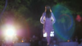 Catwalk model into high heels goes on podium in spotlight lighting at fashion week. In unfocused stock video