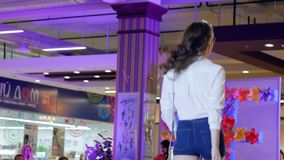 Catwalk model in shirt and denim shorts and eyeglasses, presentation of new collection of women`s clothing