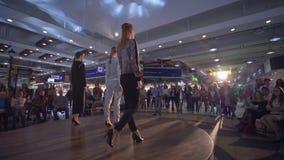 Catwalkmodeller i höga häl går på landningsbana till presentationsshowen av ny samlingskläder på modeveckan arkivfilmer