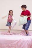 Caucásico Brother y batalla de Having Funny Pillow de la hermana en cama dentro Foto de archivo