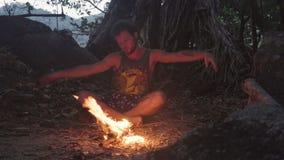 Caucásico Savage Man Burning Little Campfire en el bosque tropical en el crepúsculo para hervir la caldera con el arroz para la c almacen de metraje de vídeo
