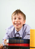 Blond schoolboy laughing with many multicolored books on grey ba. Caucaian blond schoolboy laughing with many multicolored books on grey Royalty Free Stock Image