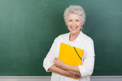 Caucaisna cheerful female senior teacher. Horizontal portrait of a Caucasian cheerful female senior teacher holding a yellow file with a blank chalkboard behind royalty free stock images