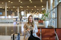 Caucasain young woman using internet by tablet in airport hall near valise. stock images