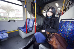 Bus Woman. Caucasian adult woman in her early 30's sitting in a rather empty articulated bus, gazing into space waiting for her stop. Her clothing suggests it's Royalty Free Stock Photography