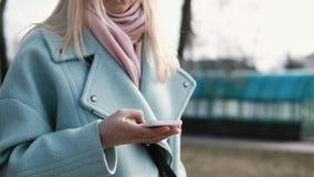 Caucasian affärskvinna som smsar på smartphonen Den nätta stilfulla blonda användande samkvämmen knyter kontakt, medan gå långsam stock video