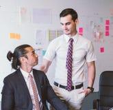 Caucasian affärsledare som lovordar underordnaden, genom att ge ett passande på skuldran med ögonkontakten Arkivbild