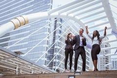 Caucasian affärsman, asiatisk affärskvinna och leende för svartaffärskvinna och lyfta upp två händer royaltyfria foton