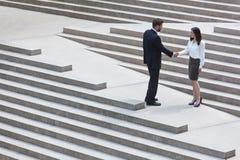 Caucasian affärsman Handshake City Steps för asiatisk kvinna Fotografering för Bildbyråer