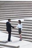 Caucasian affärsman Handshake City Steps för asiatisk kvinna royaltyfri bild