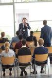 Caucasian affärsman som gör ett anförande i konferensrum arkivbild